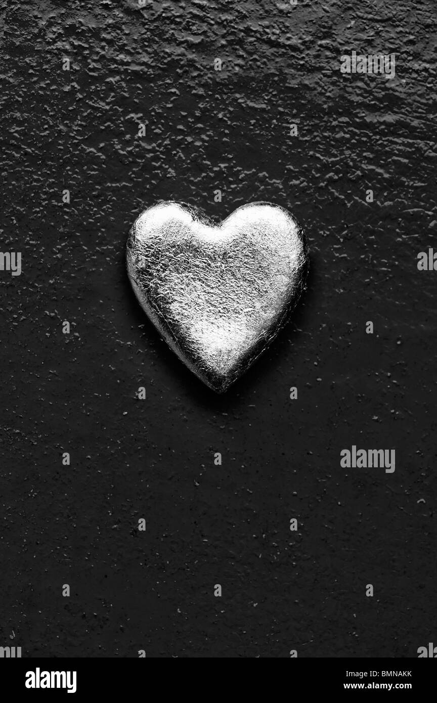 Forme de coeur en or contre metal texture monochrome. Photo Stock
