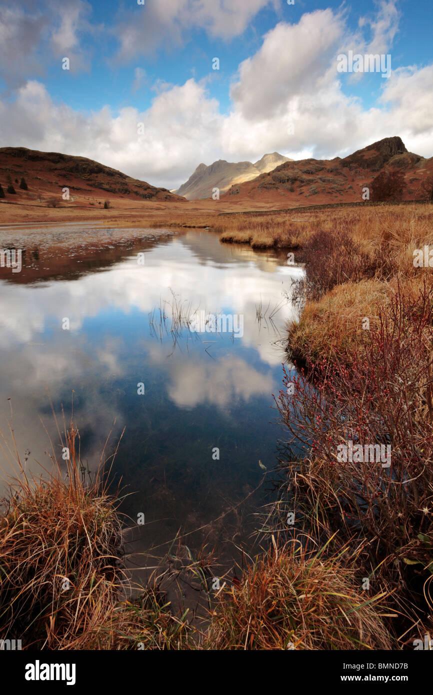 Ciel bleu et nuages reflétée dans le Tarn Blea avec The Langdales dans la distance Banque D'Images