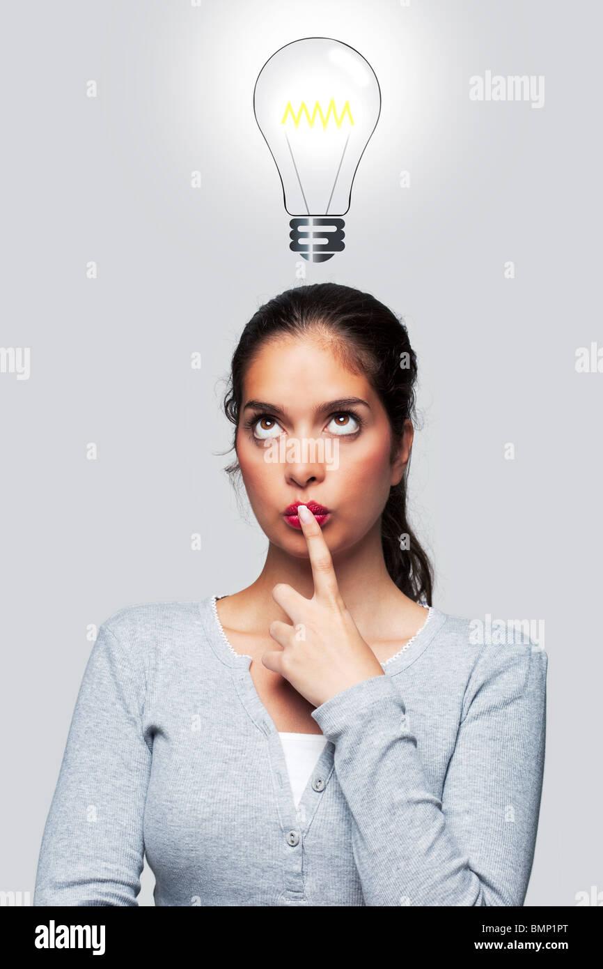 Notion de droit d'une femme avec une idée lumineuse, illustration d'une ampoule au-dessus de sa tête. Photo Stock