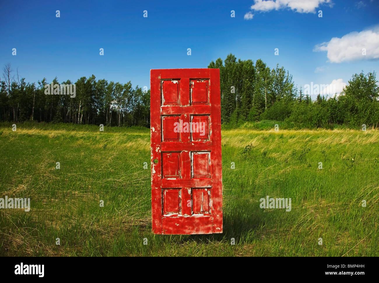 L'Alberta, Canada; un vieux, usé dans un domaine porte rouge Photo Stock