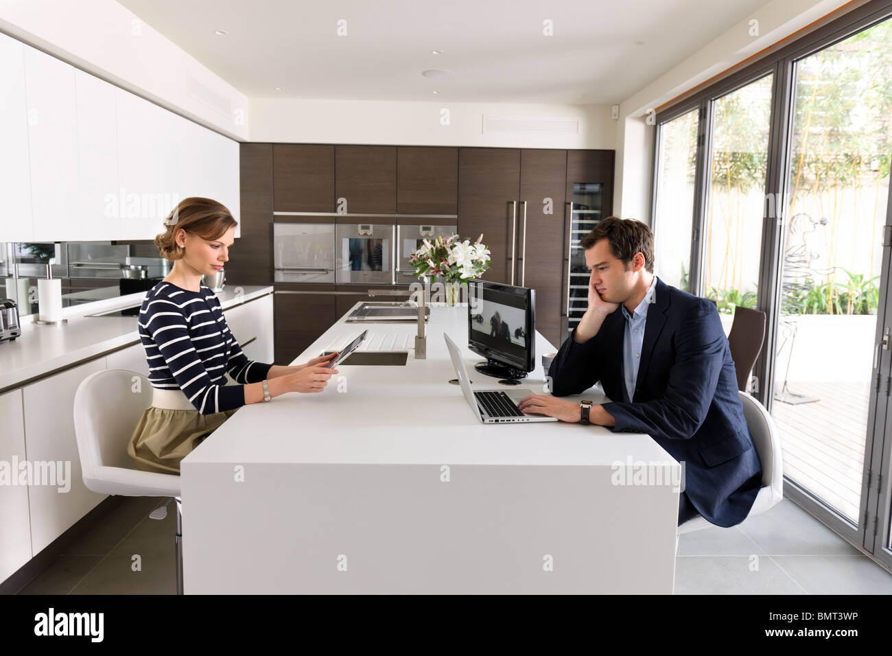 Couple looking at laptop et l'ipad dans leur cuisine de haute technologie. Photo Stock