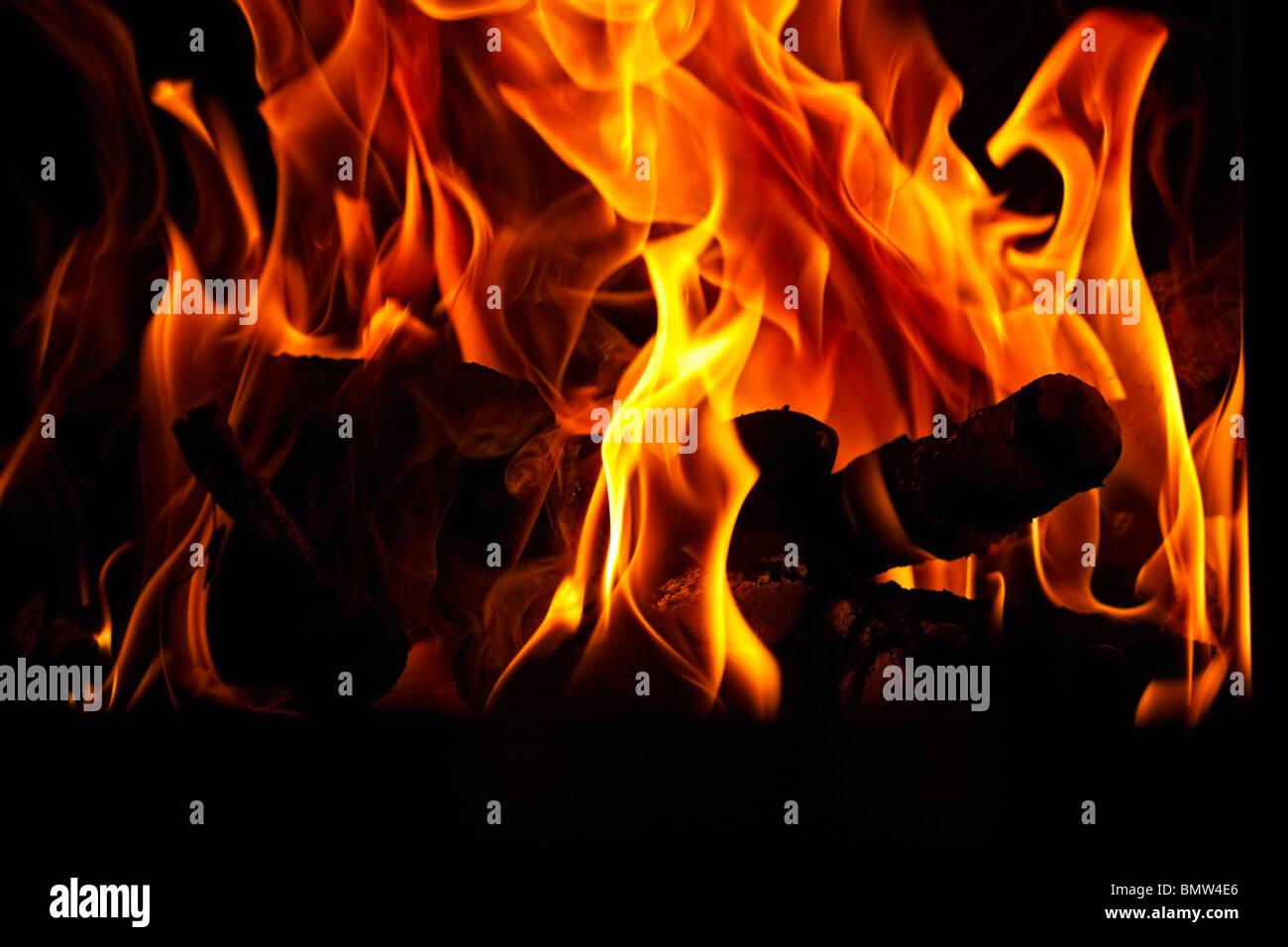 Bûches silhouetté contre flammes dans un foyer. Photo Stock