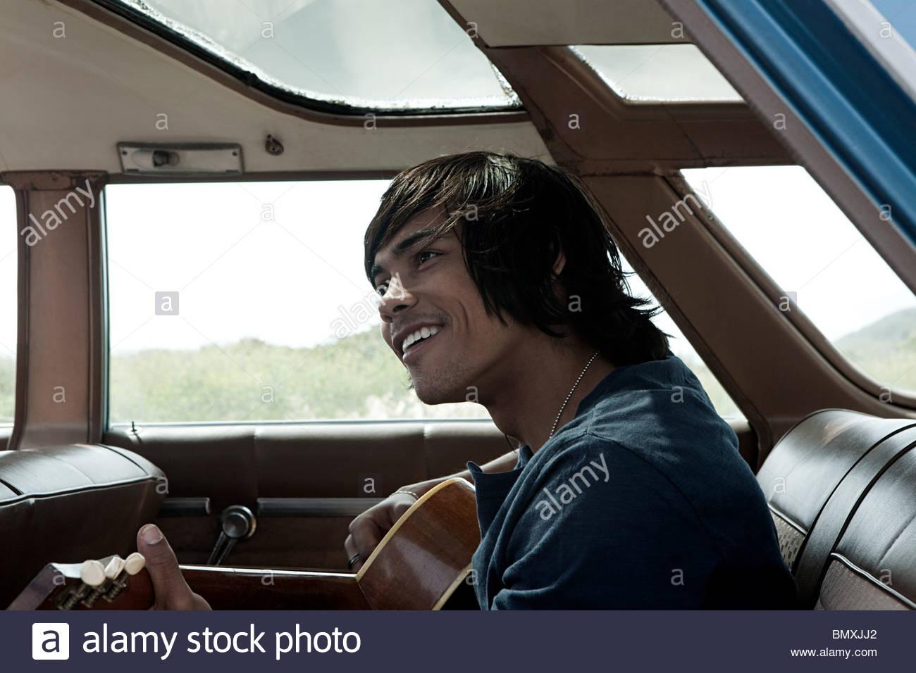 Jeune homme à l'intérieur de voiture à jouer de la guitare Photo Stock
