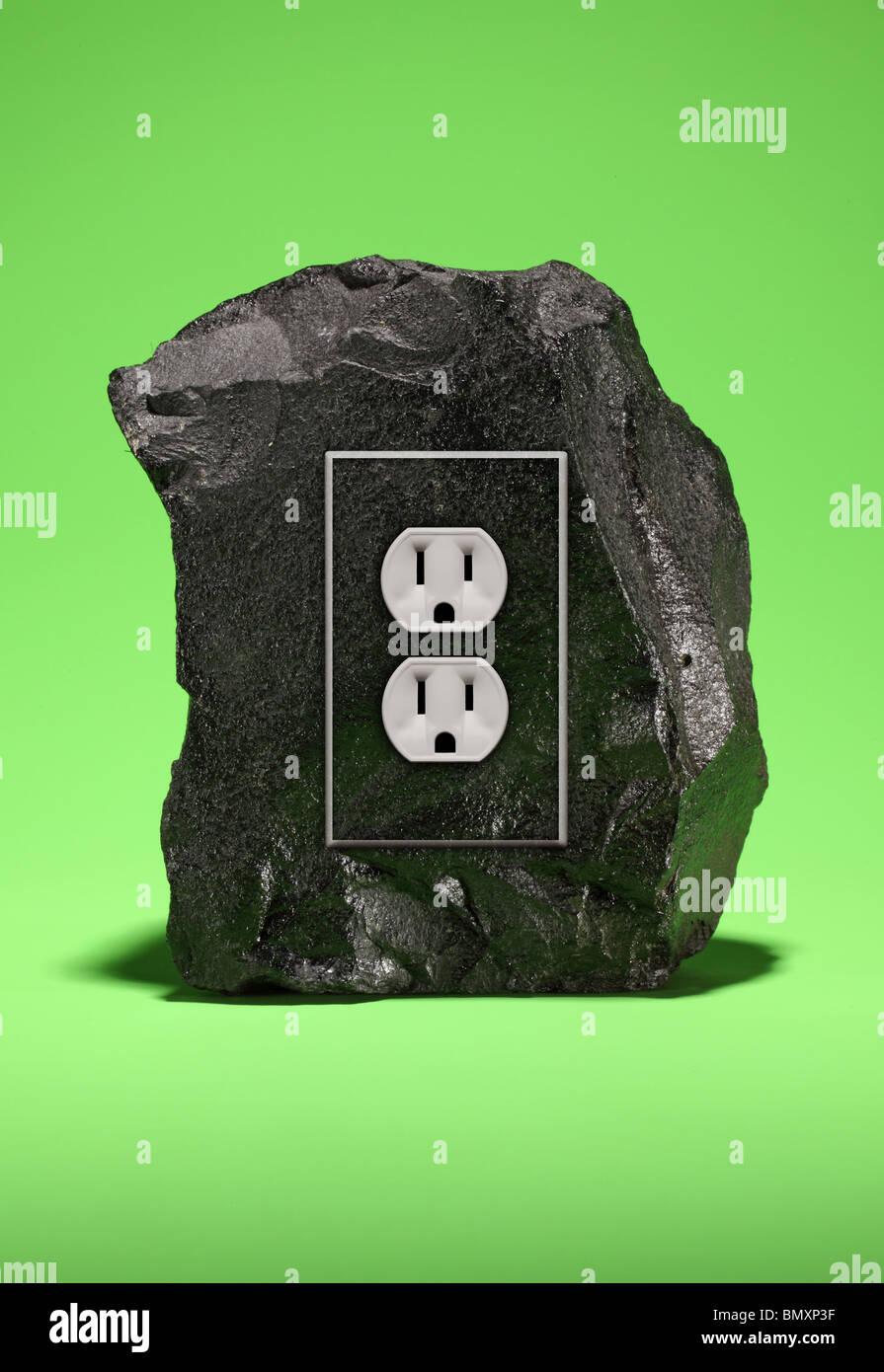 Un grand morceau de charbon avec un dispositif de prise de courant électrique sur un fond vert. Photo Stock