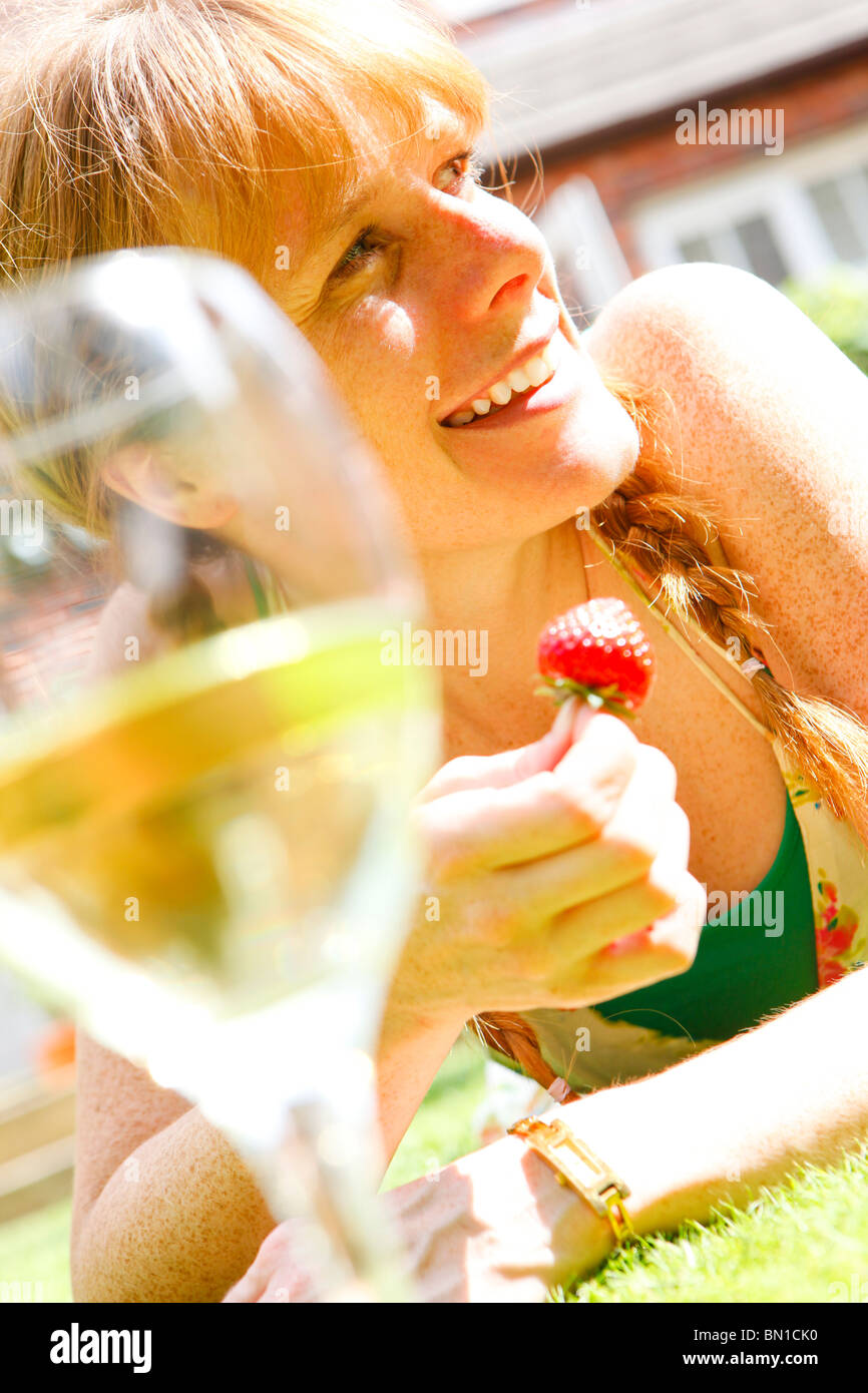 Femme d'une trentaine de boire un verre de vin et de manger dans son jardin de fraises Photo Stock