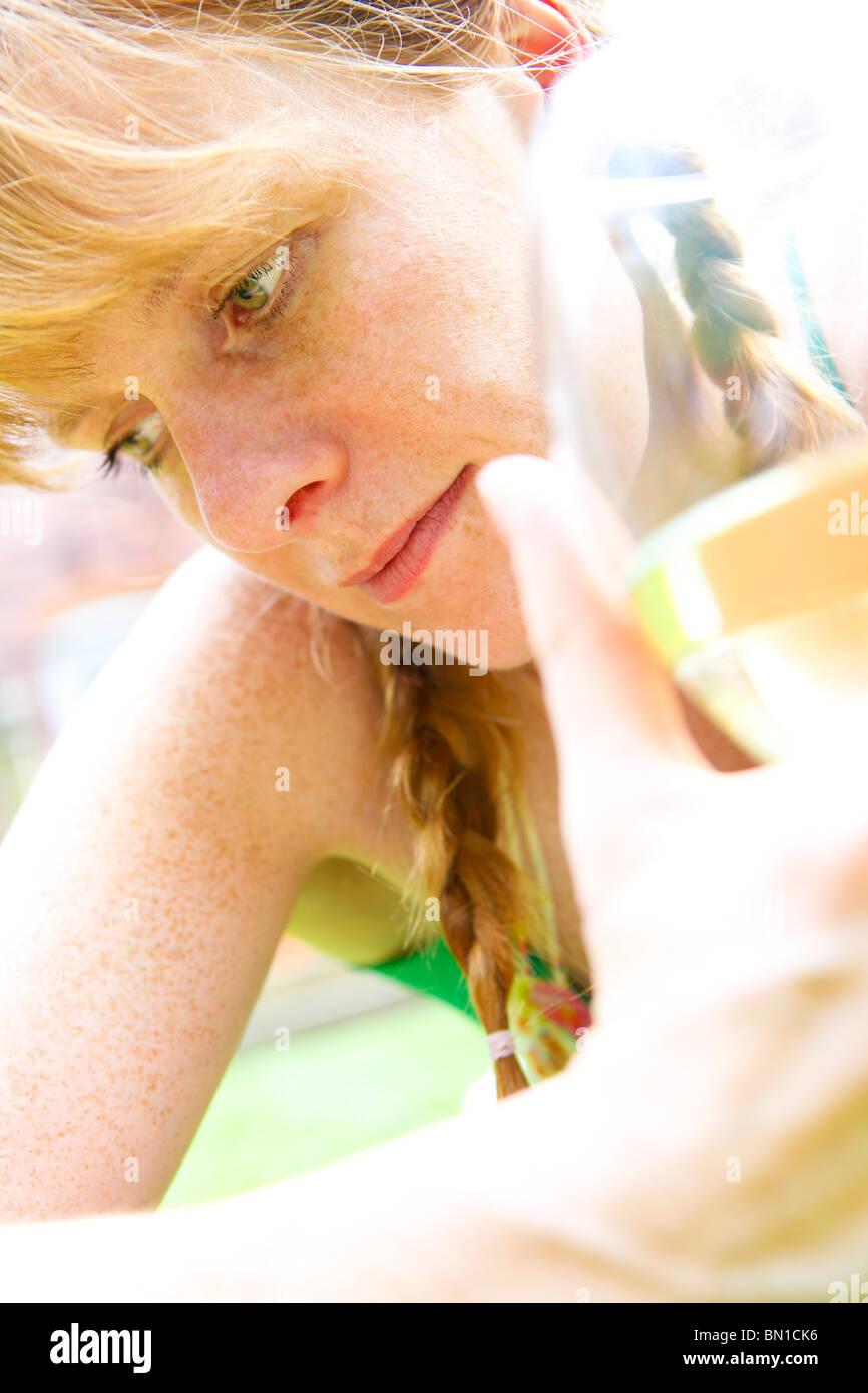Femme d'une trentaine de boire un verre de vin dans son jardin Photo Stock