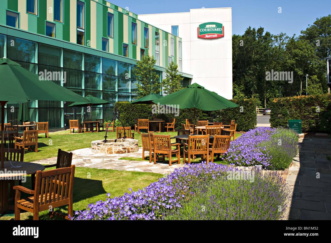 Petit jardin fleuri et une terrasse avec parasols et chaises ...