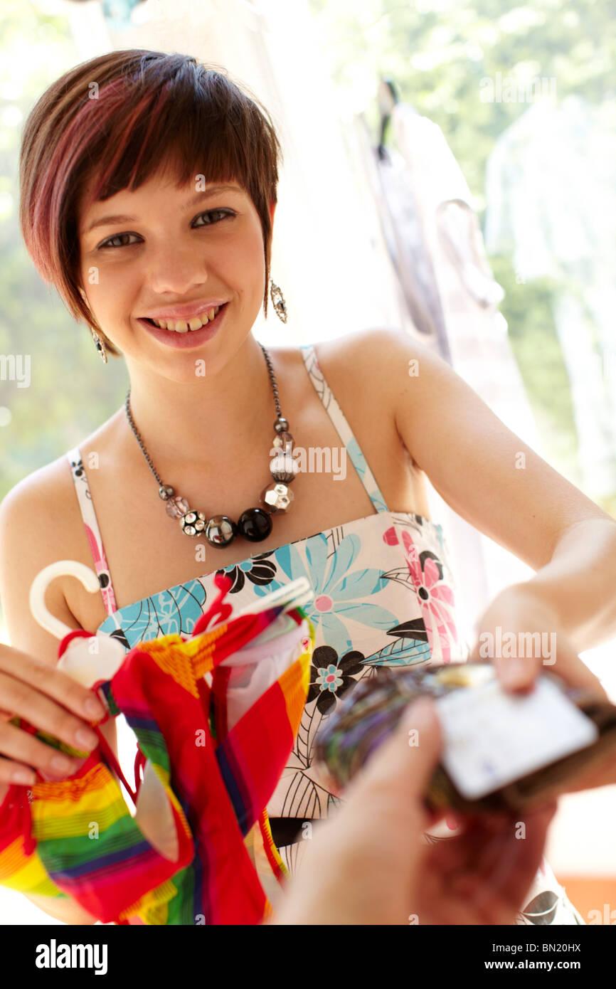 Girl le paiement des biens en boutique Photo Stock