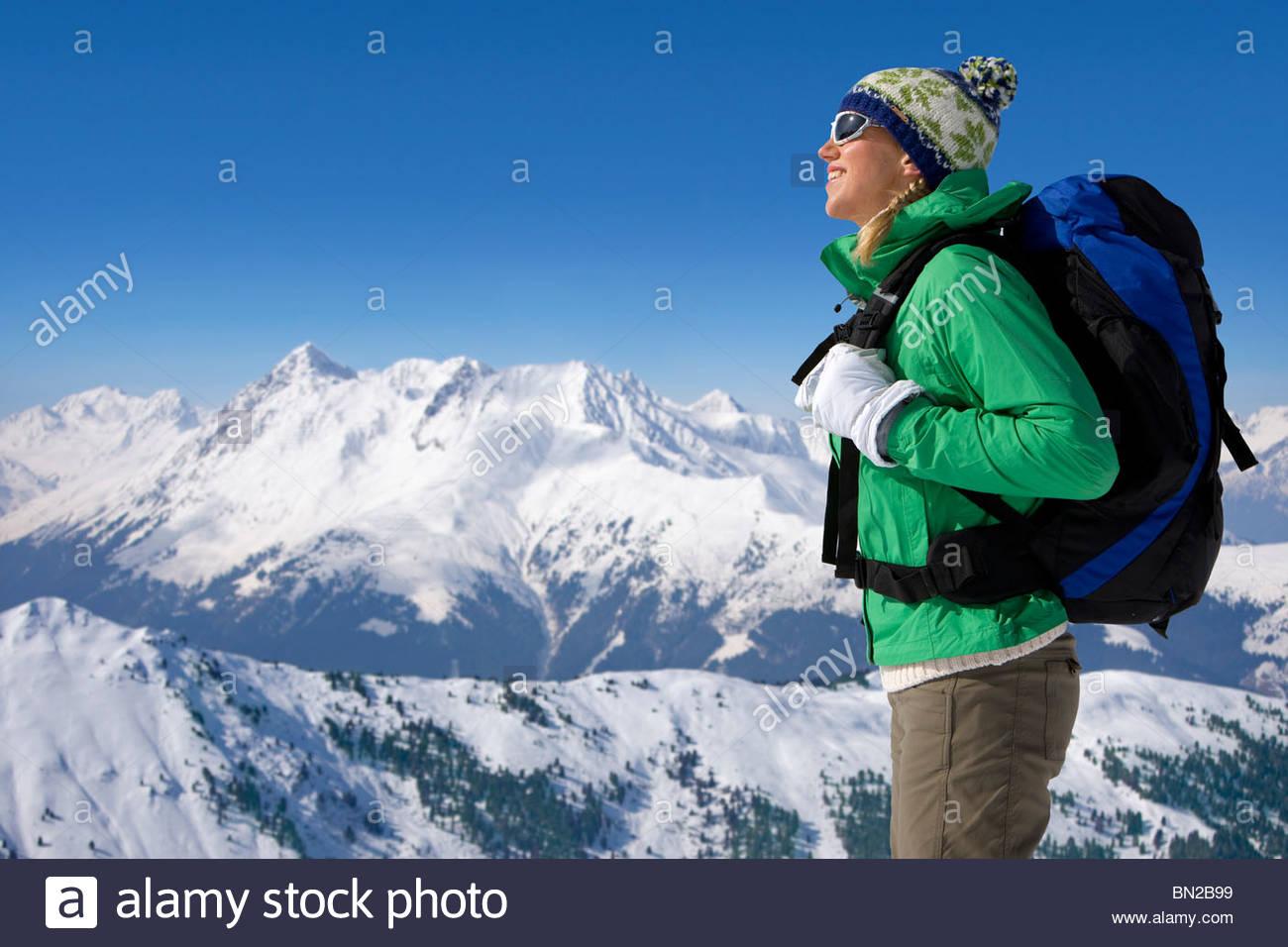 Femme avec sac à dos sur la montagne enneigée Photo Stock