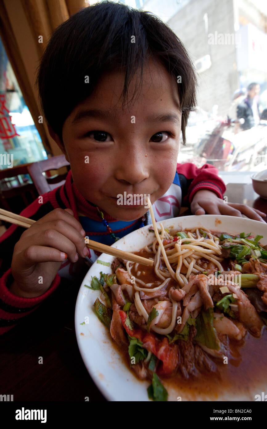 Boy eating noodles à Shigatse, Tibet Photo Stock