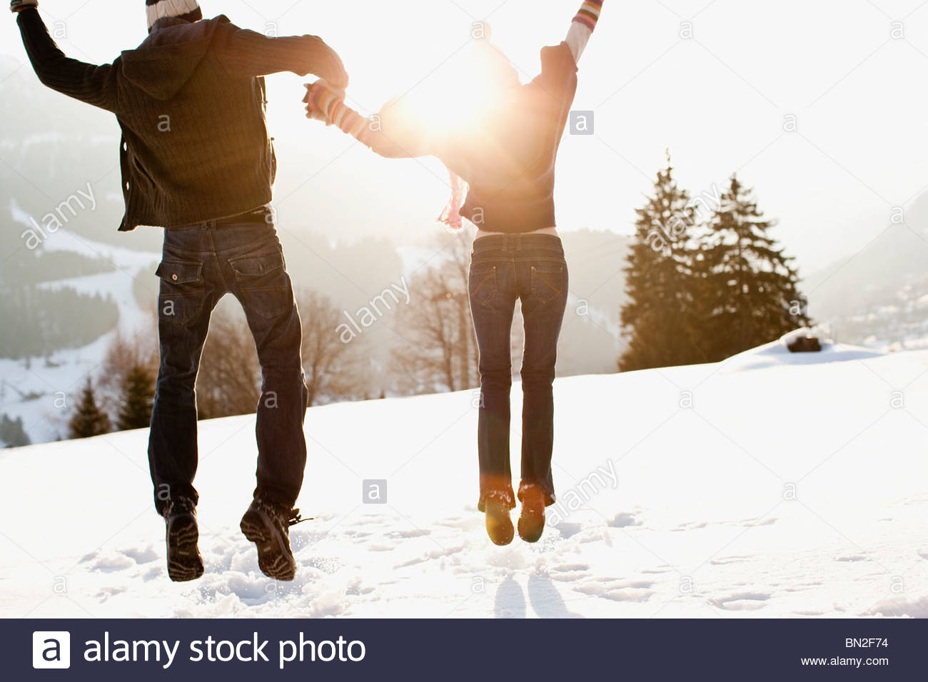 Couple jumping outdoors in snow Banque D'Images