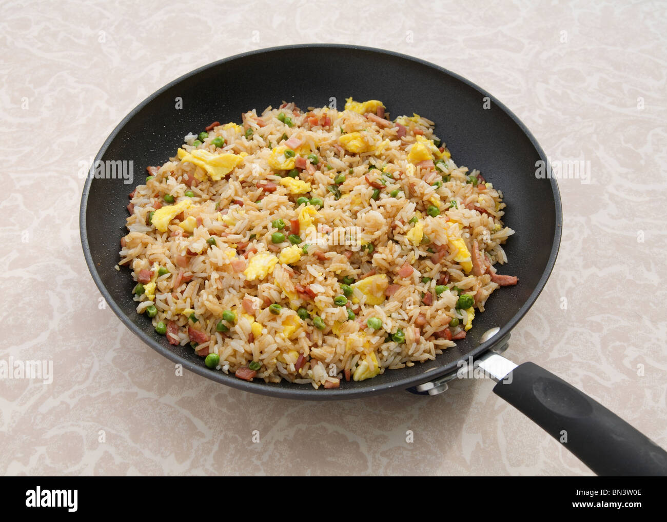Poêle, casserole pleine de riz frit au jambon colorés Photo Stock