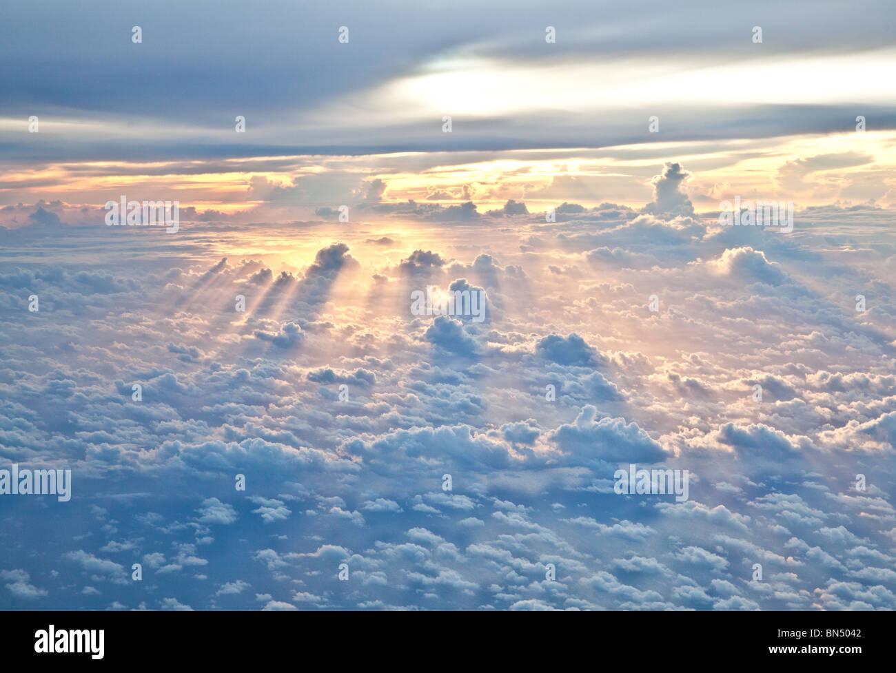 Les rayons du soleil brillent à travers les nuages comme approches crépuscule Photo Stock