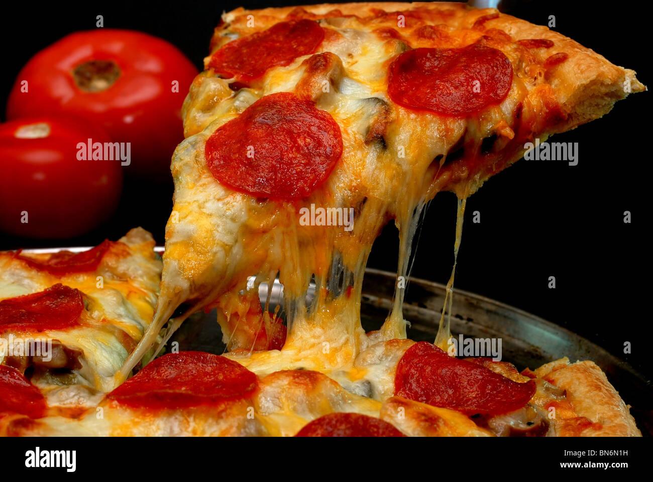 Tranche de pizza au pepperoni, retiré de pizza entière avec des tomates en arrière-plan. Isolé sur fond noir. Banque D'Images