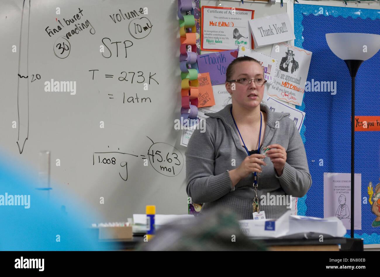 Femelle Anglo high school science l'enseignant explique les procédures d'expérimentation en classe. Photo Stock