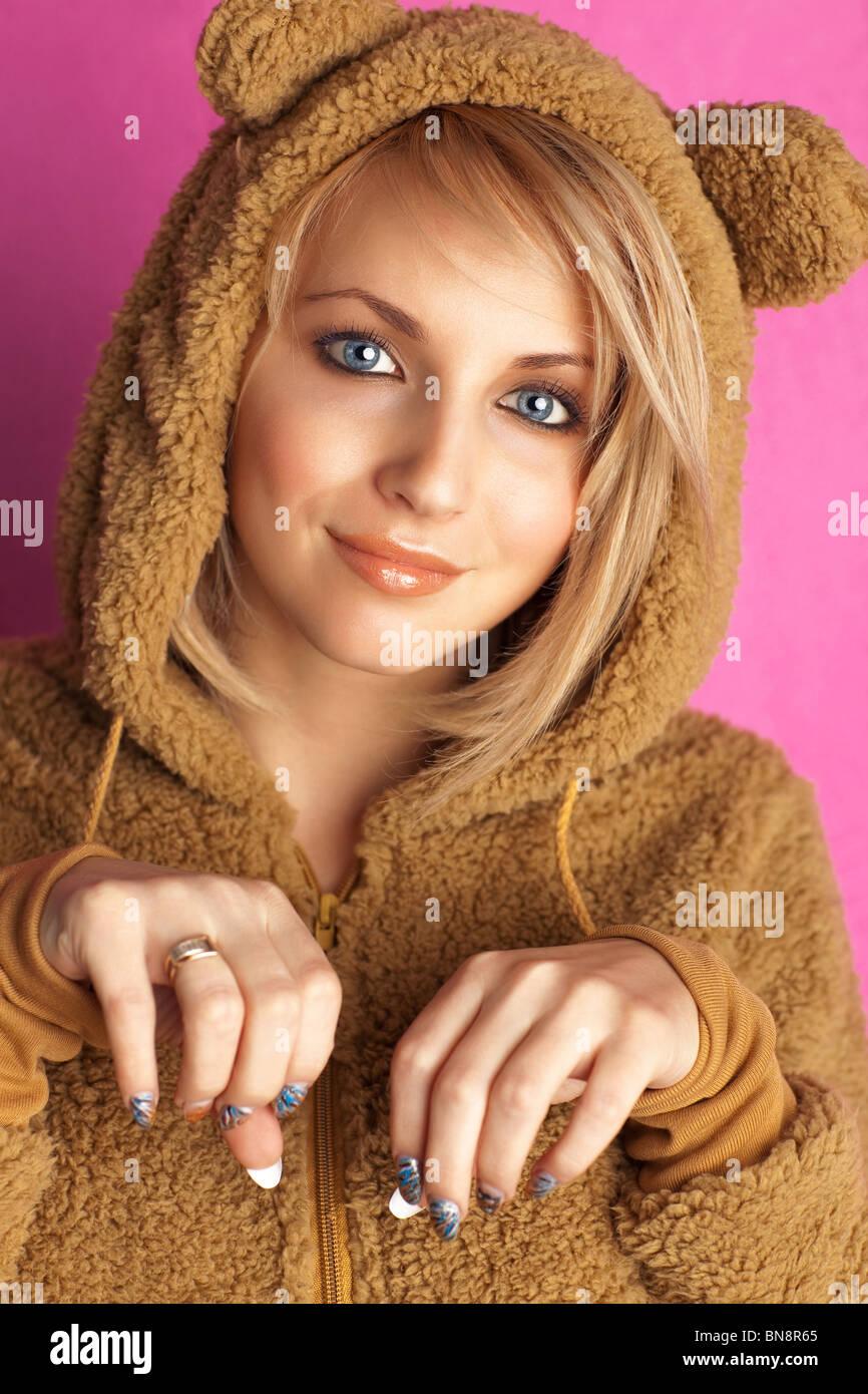 Jeune femme en costume d'ours. Sur fond rose. Photo Stock