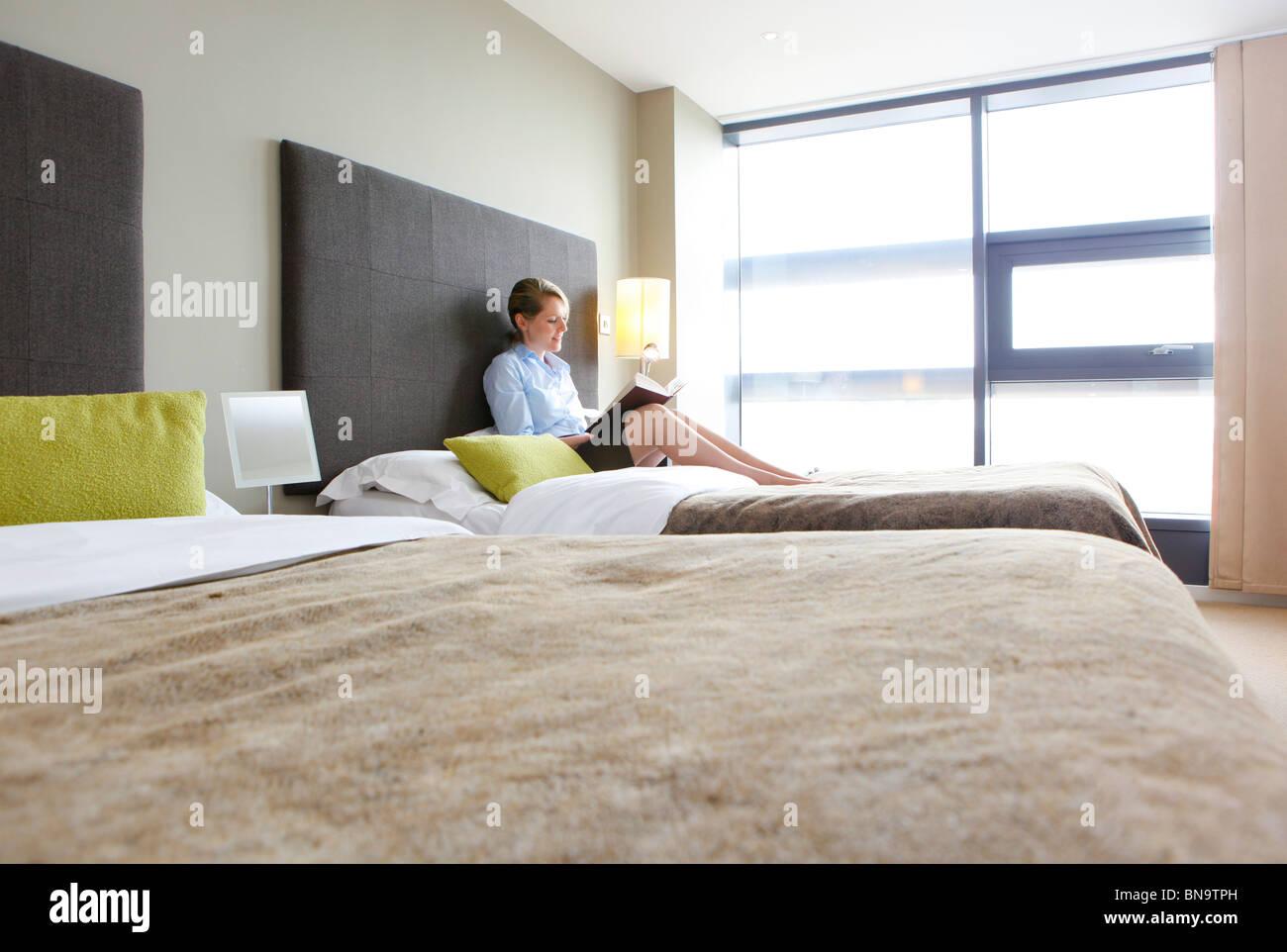 Femme lisant un livre assis sur un lit dans un appartement, Photo Stock