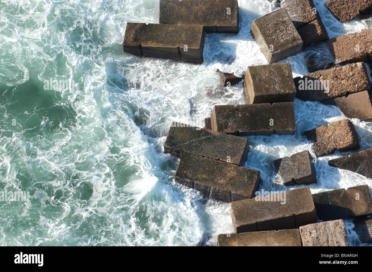 Surfez livres sur des blocs de ciment utilisés pour dissiper l'énergie des mers en une rupture mur. Photo Stock