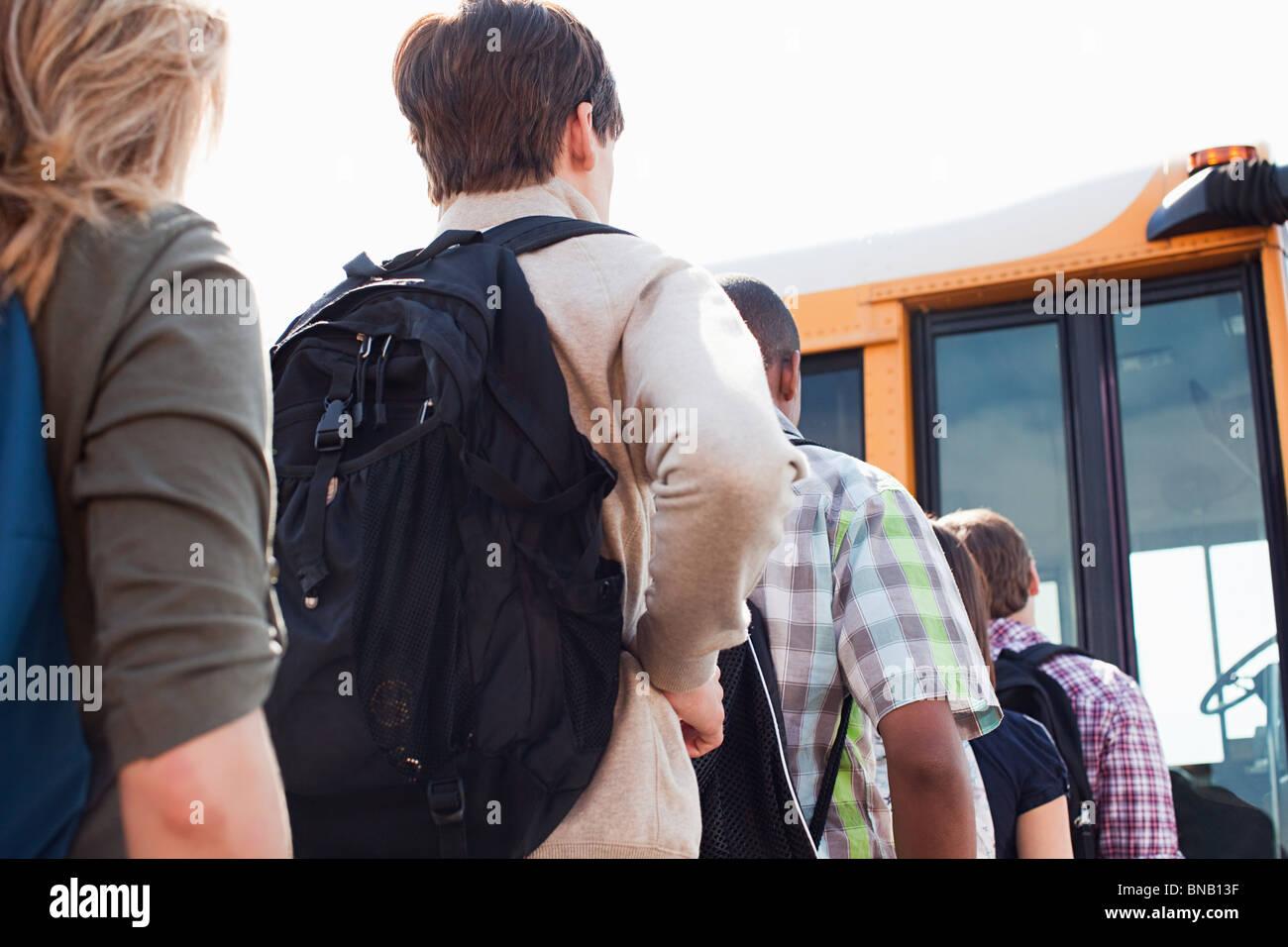 Les élèves du secondaire d'attente pour les autobus scolaires Photo Stock