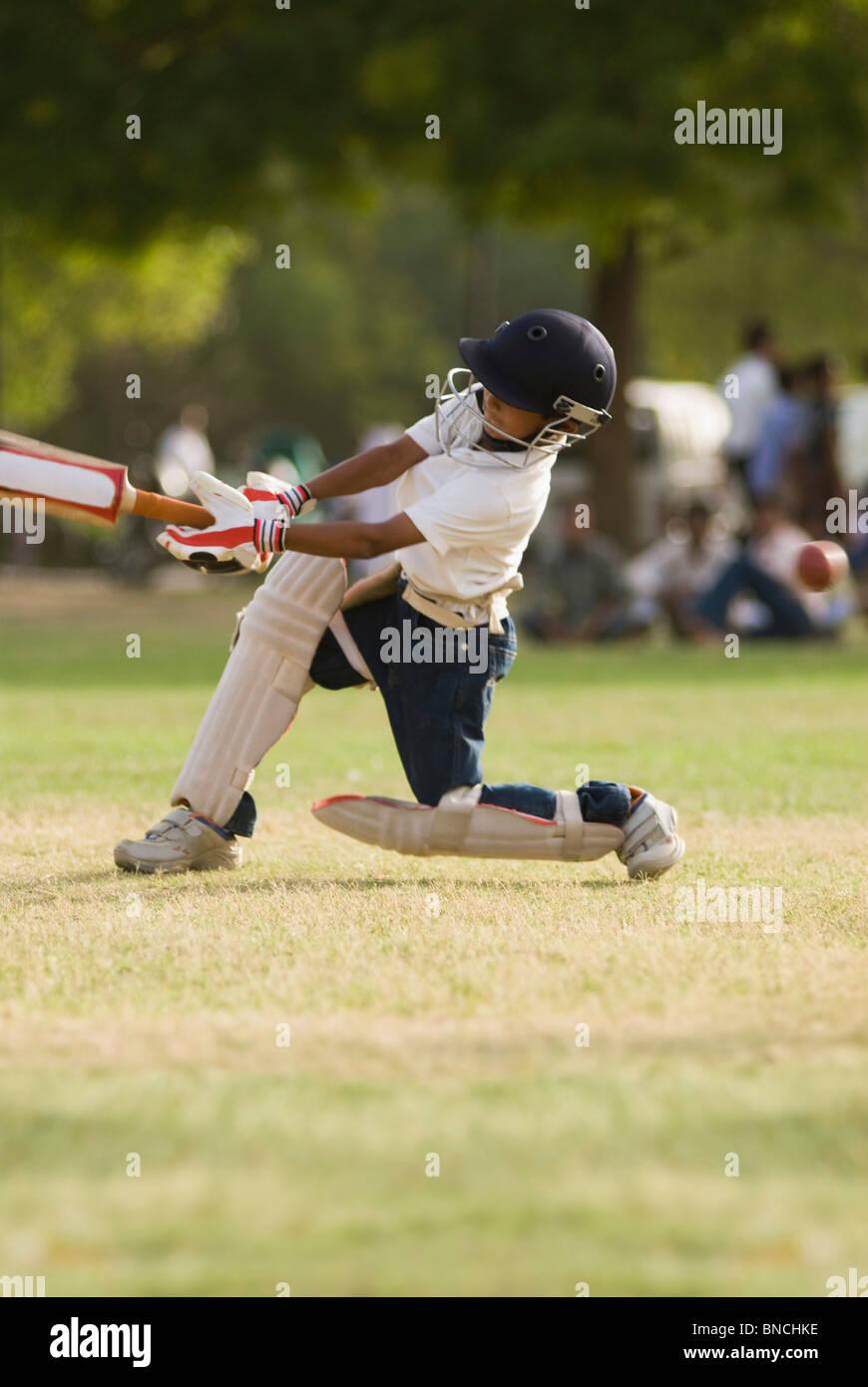 Garçon à jouer au cricket dans une aire de jeux, New Delhi, Inde Photo Stock