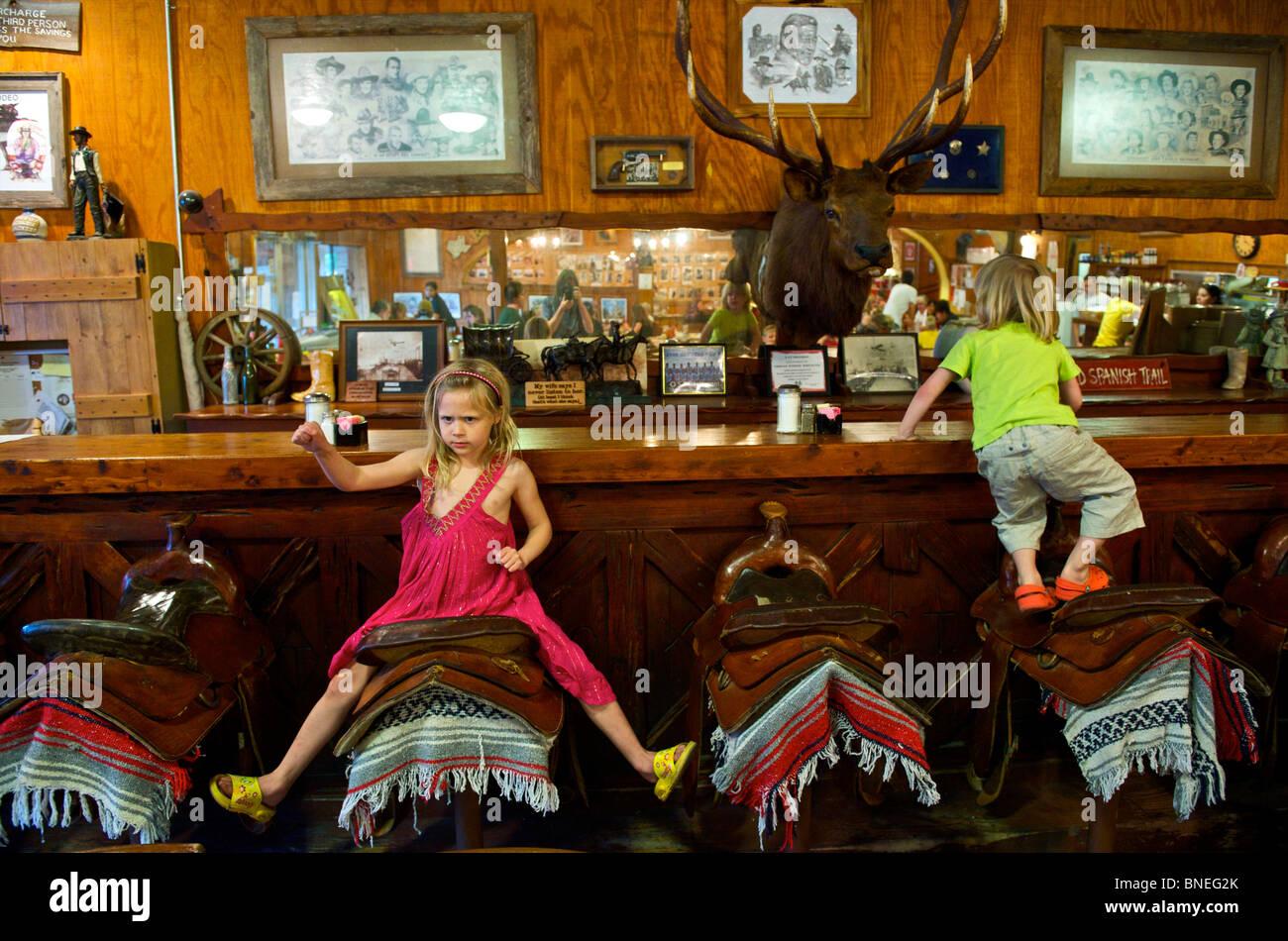 Les enfants jouant sur les outils de la Selle Bar espagnol, Texas Hill Country, Bandera, Texas, USA Banque D'Images