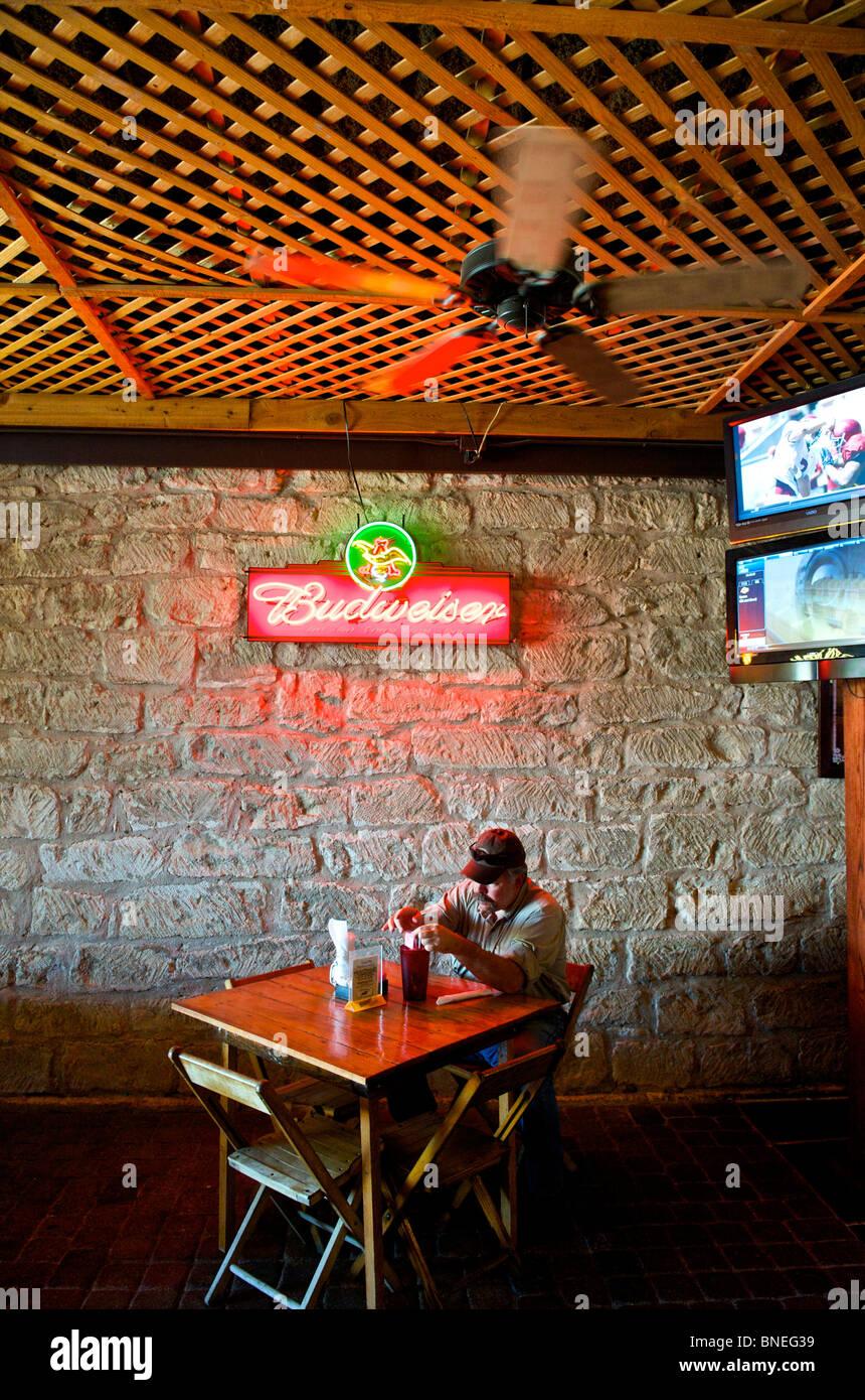Un homme assis seul dans le restaurant Biergarten Auslander et Hill Country Fredericksburg, au Texas, USA Banque D'Images