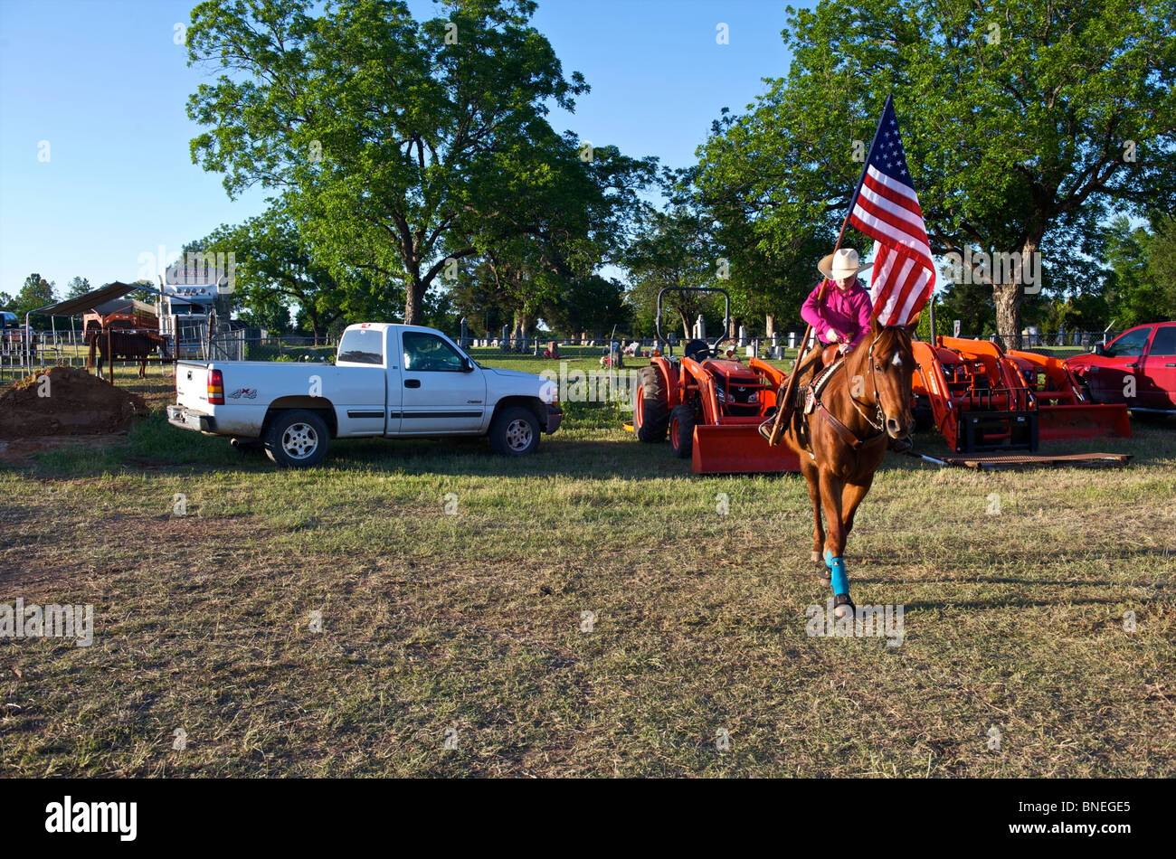 Cowgirl waving flag en bestiaux avant la cérémonie d'ouverture de l'érythroblastopénie événement rodéo au Texas, USA Banque D'Images