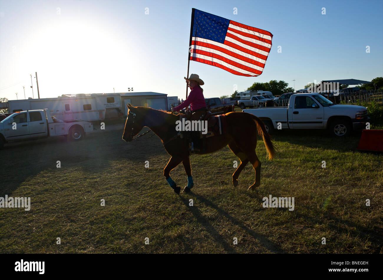 Cowgirl en agitant le drapeau américain à la cérémonie d'ouverture de l'érythroblastopénie événement rodéo au Texas, USA Banque D'Images