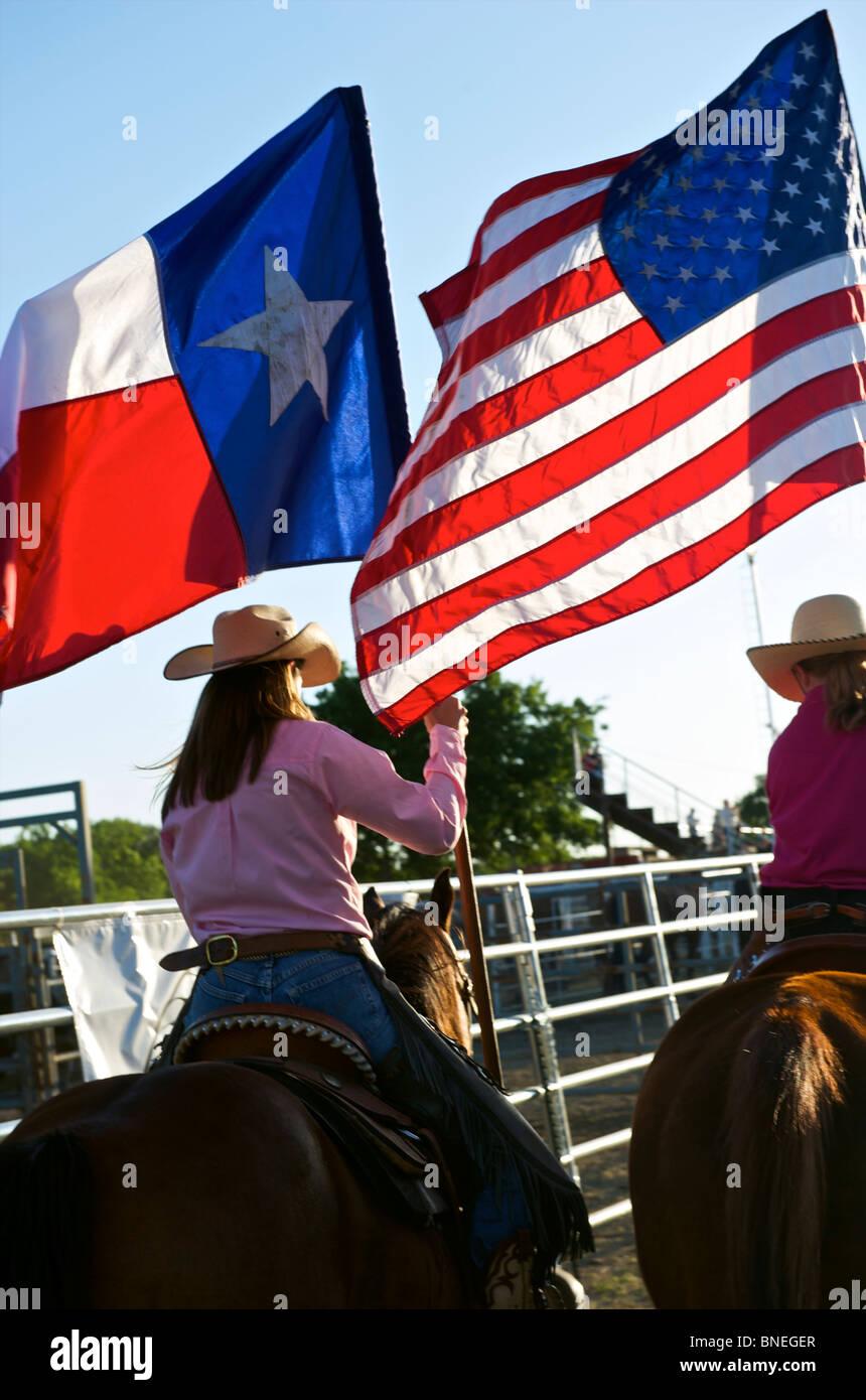 Cowgirls waving flag en bestiaux sur la cérémonie d'ouverture de l'érythroblastopénie événement rodéo au Texas, USA Banque D'Images