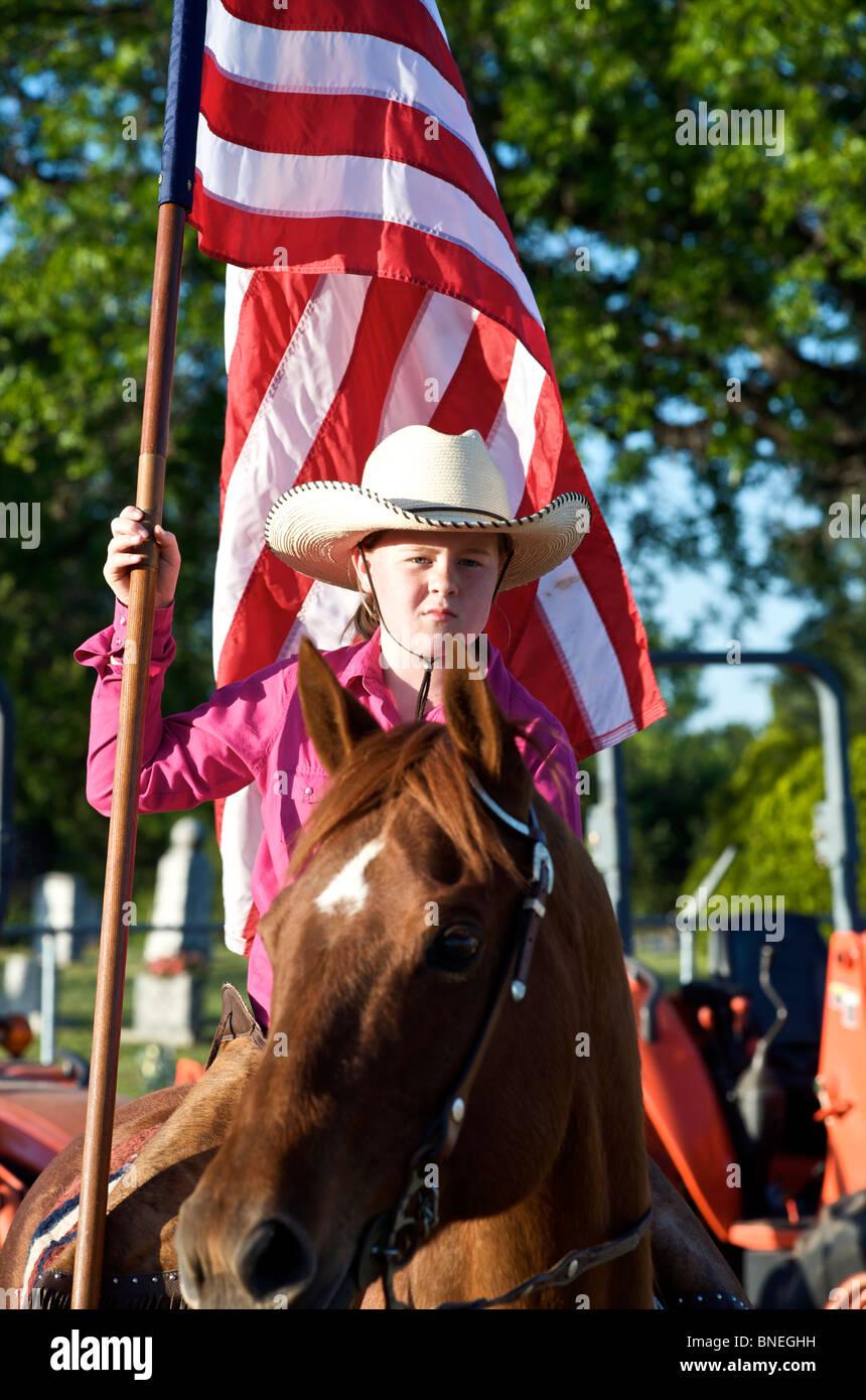 Cowgirl en agitant drapeau américain à l'érythroblastopénie événement rodéo au Texas, USA Banque D'Images
