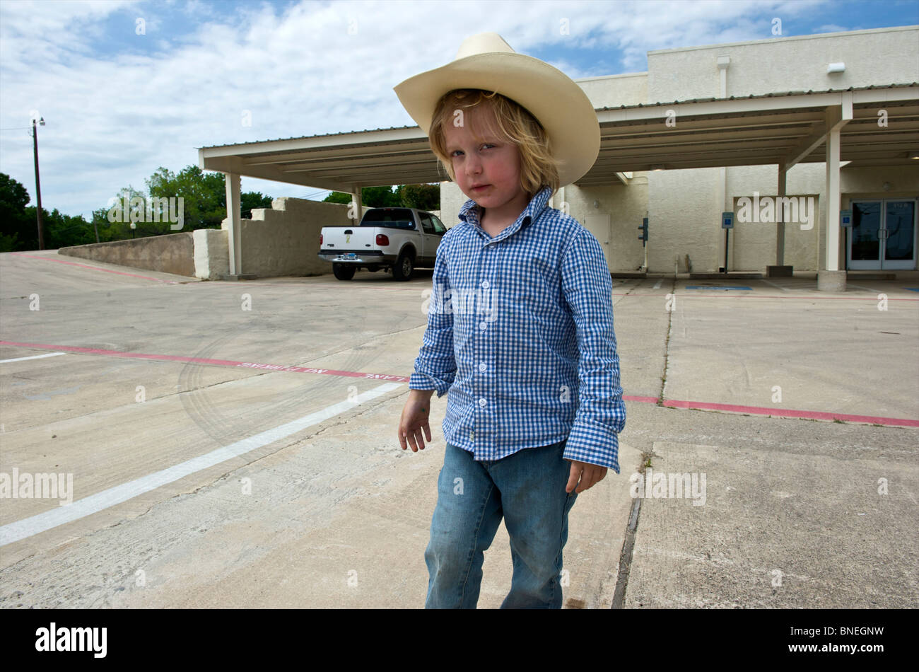 Jeune cowboy posing in front of building à Petite-ville Texas, États-Unis Banque D'Images