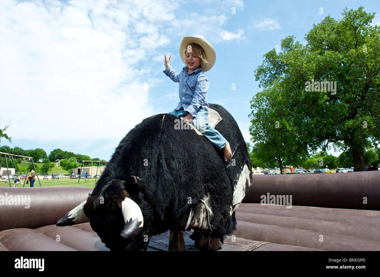 Avec: essayer sa chance de rester sur le taureau mécanique Banque D'Images