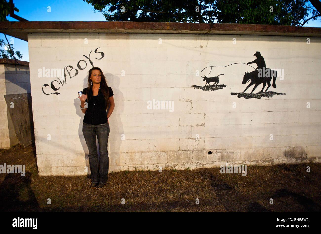 Femme debout en face des toilettes d'une petite ville PRCA Rodeo Bridgeport, Texas, États-Unis Banque D'Images