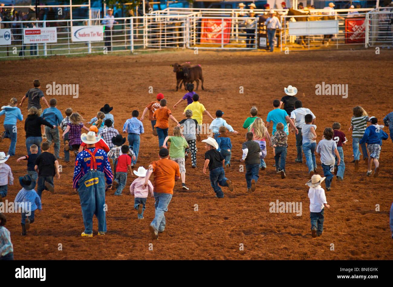 Jeune foule courir pour attraper les chargeuses à PRCA Rodeo à Petite-ville Bridgeport, Texas, États-Unis Banque D'Images