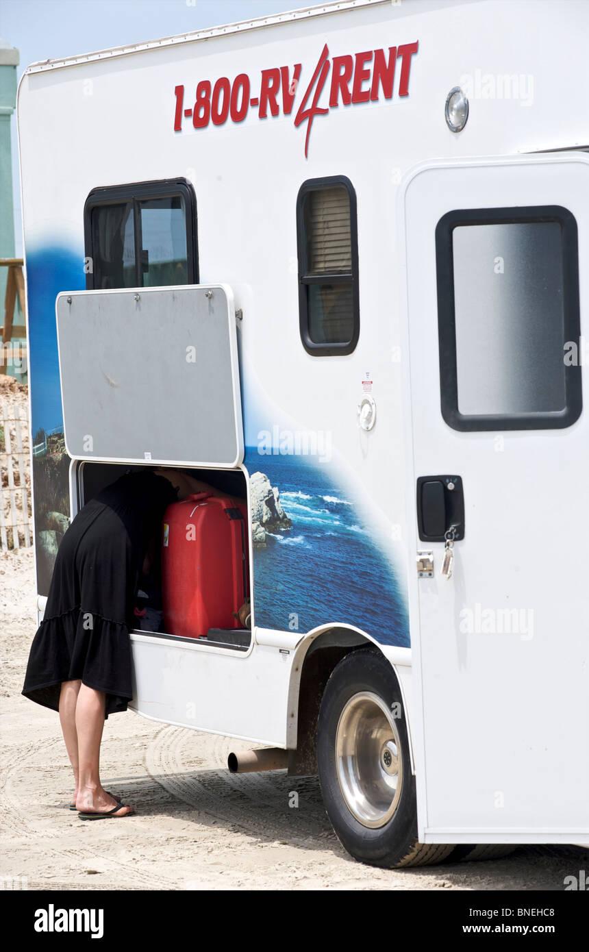 Jeune fille à la recherche de quelque chose dans le coffre d'une voiture de camping-campervan RV sur un camping dans le Texas, USA Banque D'Images