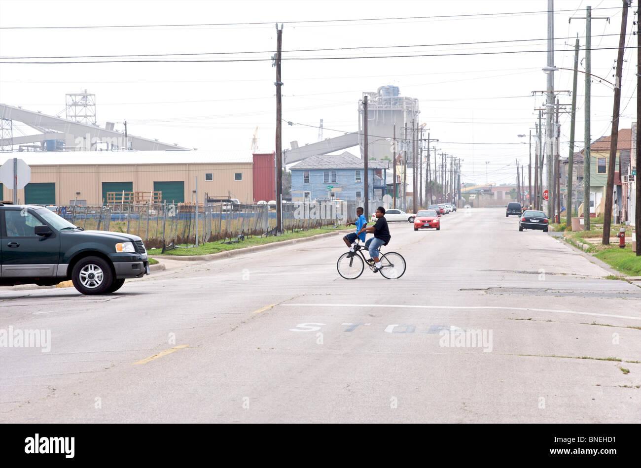 Les enfants à vélo crossing road près de quartier pauvre de Galveston, Texas, États-Unis Banque D'Images