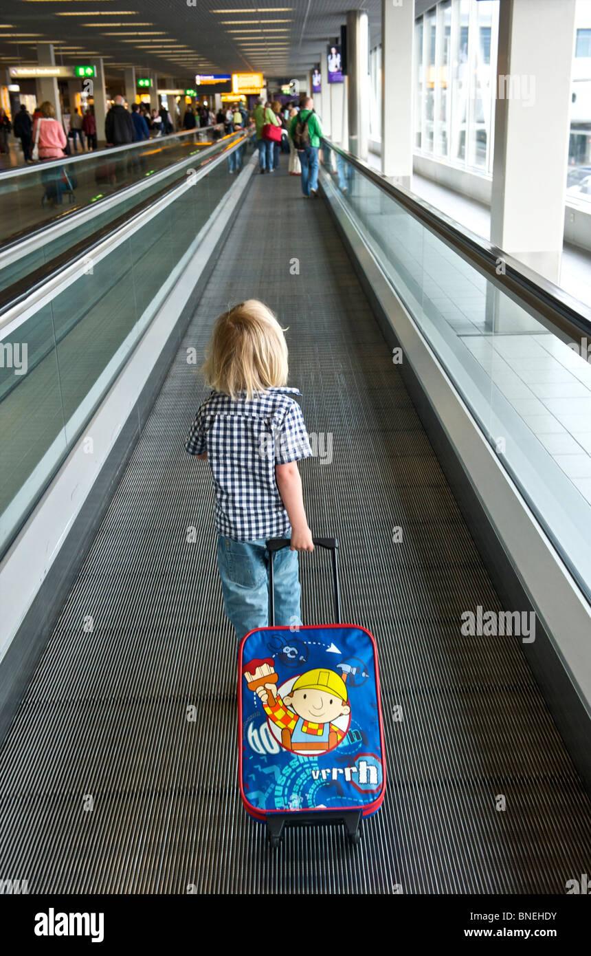 Trois ans sur son chemin vers le hall des départs à l'aéroport de Schiphol en Pays-bas, Europe Banque D'Images
