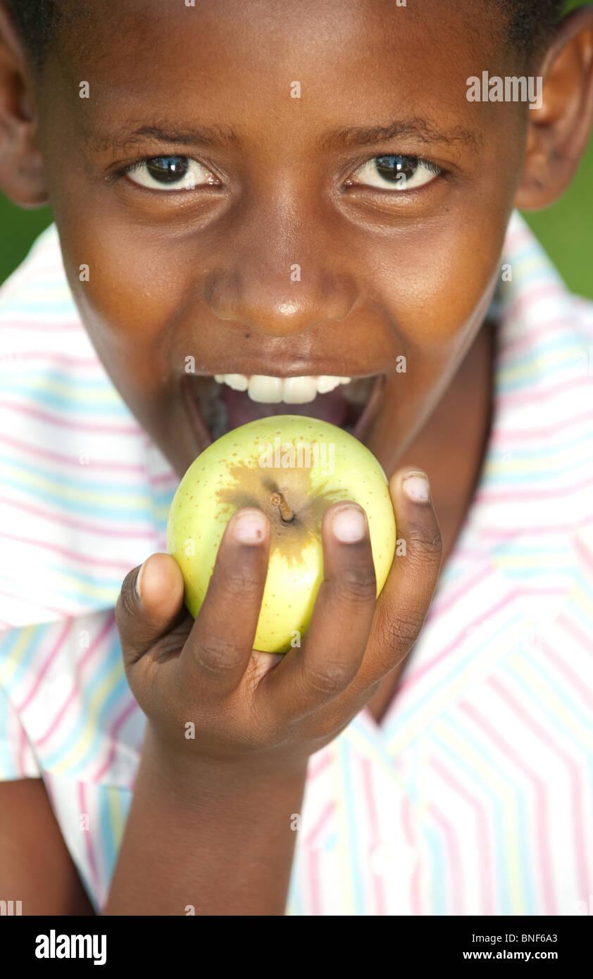 Portrait of Girl (8-9) biting apple, Johannesburg, la Province de Gauteng, Afrique du Sud Photo Stock