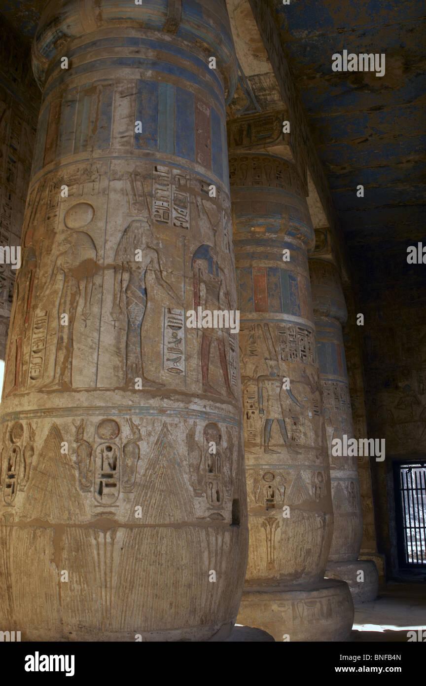 Temple de Ramsès III. Colonnes décorées de reliefs polychromé. L'Égypte. Banque D'Images