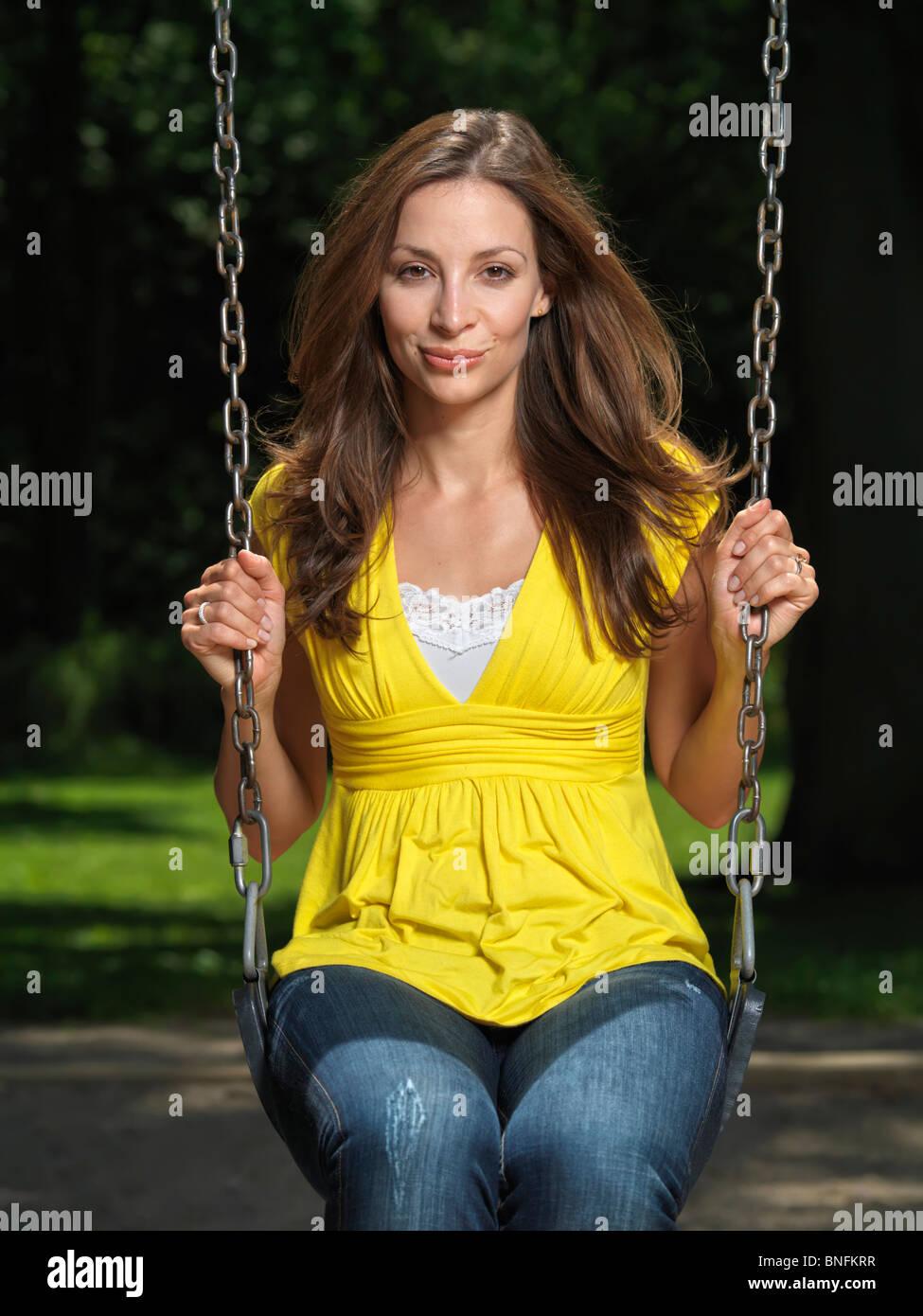 Young smiling attractive femme assise sur une balançoire dans un parc Banque D'Images