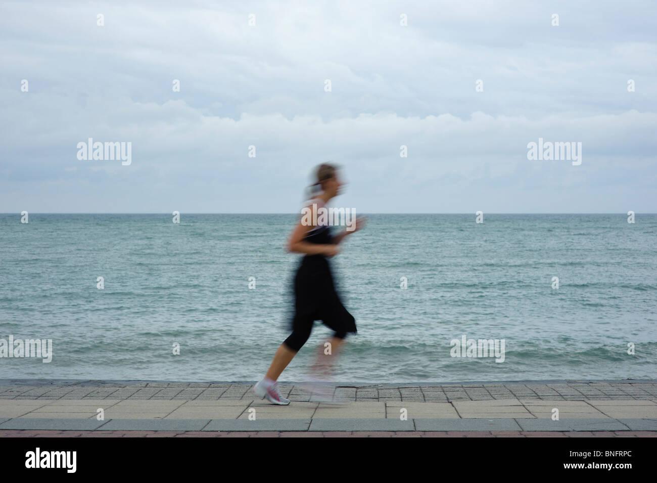 Flou de mouvement, une femme jogger running jogging runner par le bord de mer et ciel couvert journée grise Photo Stock
