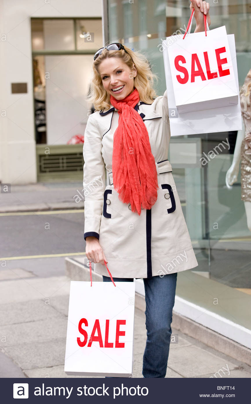 A mid adult woman holding up certains vente sacs, smiling Photo Stock
