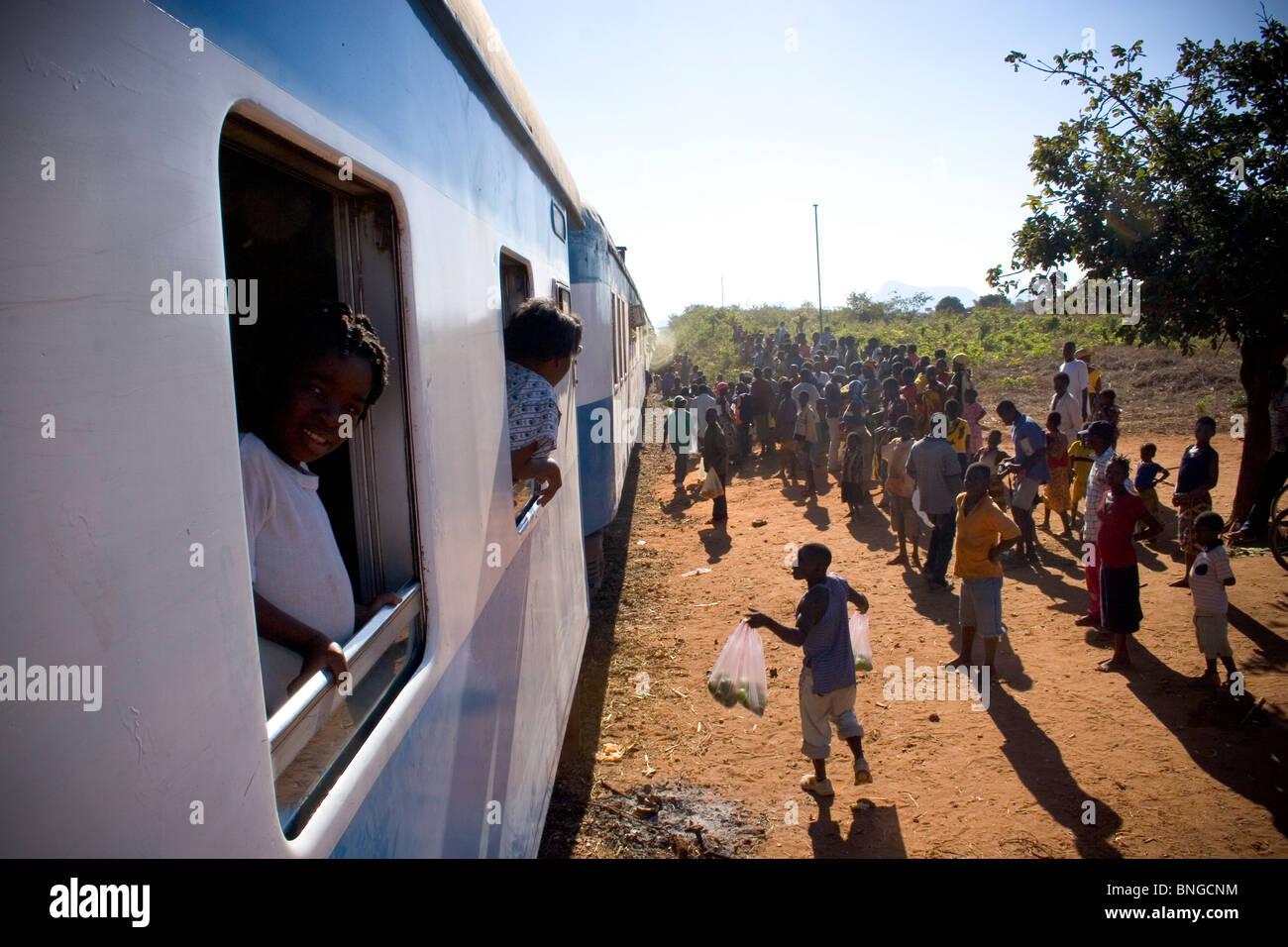 Les villageois et les vendeurs locaux accueillir le train à l'un de ses nombreux arrêts entre Nampula Photo Stock