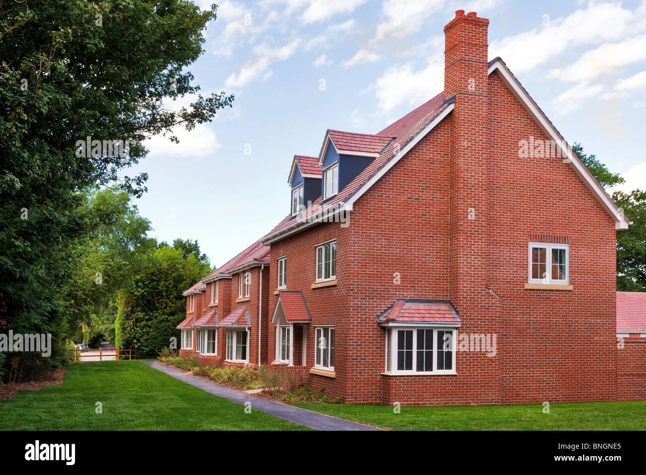 Une rangée de nouvelles maisons en brique rouge vide sur un développement immobilier de l'habitation Photo Stock