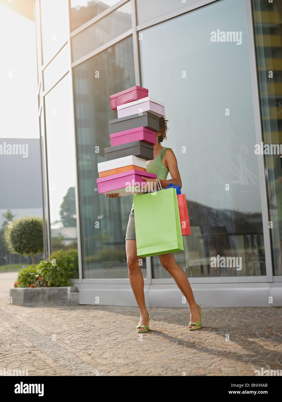 Hispanic woman balancing pile de boîtes à chaussures hors de centre commercial. La forme verticale, pleine Photo Stock