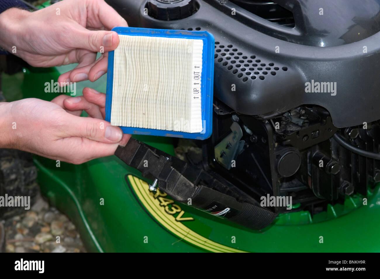 Dépose du filtre à air du moteur à essence d'une tondeuse rotative Photo Stock