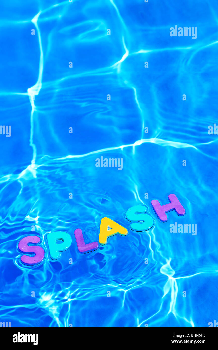 Le mot SPLASH en mousse lettres flottant à la surface de l'eau d'une piscine Photo Stock