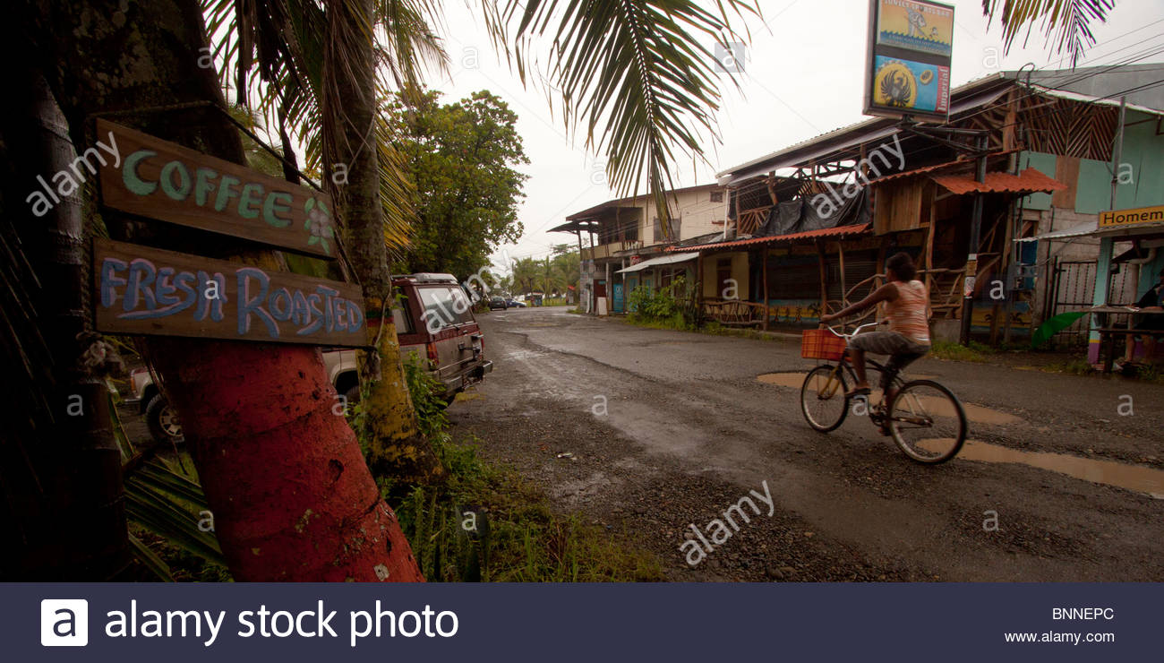 Girl riding son vélo sur un chemin de terre du centre-ville de Puerto Viejo, Costa Rica Photo Stock