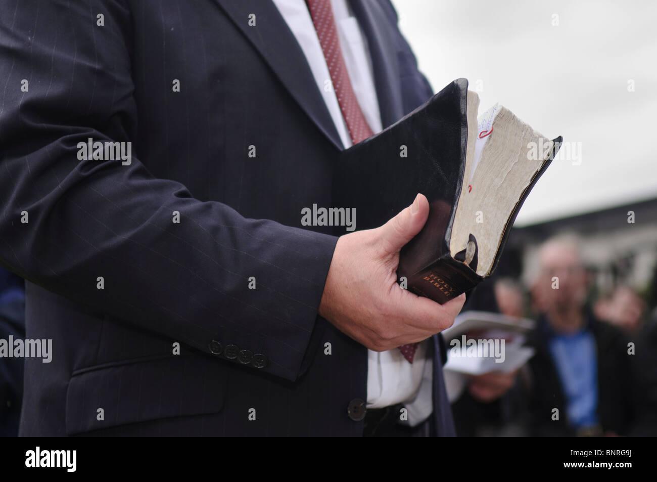 Ministre la tenue d'une grande, bien utilisé bible Banque D'Images