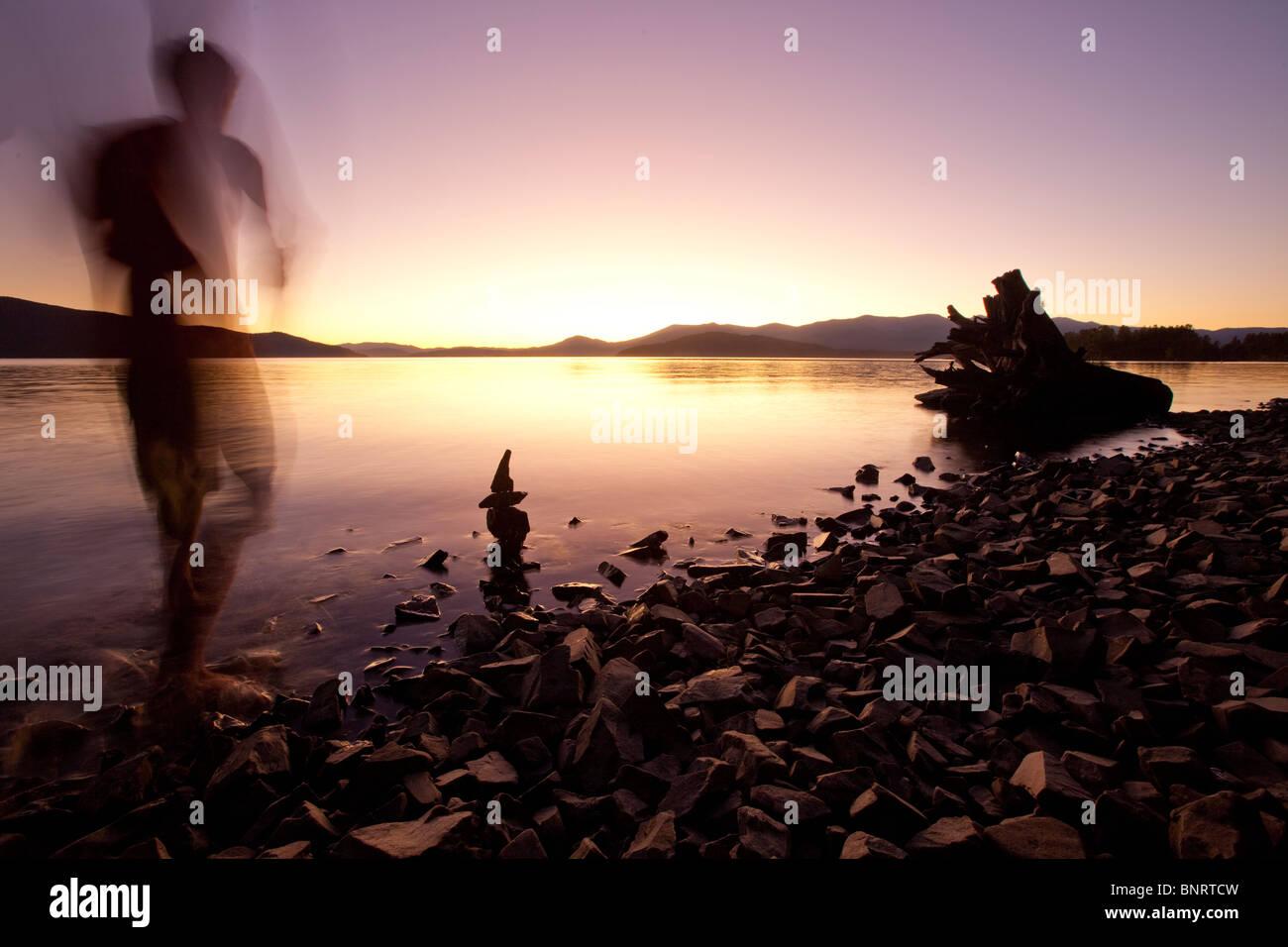 Une figure masculine en regardant le coucher de soleil sur un lac et les montagnes de l'Idaho. Photo Stock